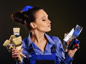 Builder woman holding paint brushes . Fashion