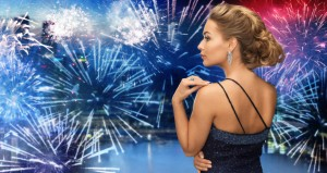 people, holidays, party, jewelry and glamour concept - beautiful woman with diamond earring over firework lights in city background